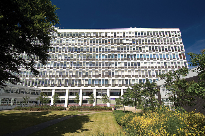 picture of University of Brighton cockcroft building set against blue sky and framed by trees